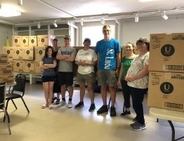volunteers stand in front of 60,000 feminine hygiene products in a storage room